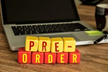 Pre-Order written on a wooden cube in front of a laptop